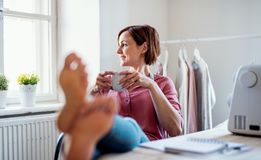 Young creative woman in a studio, resting. A startup of tailoring business. Young creative woman with coffee in a studio, resting with feet on desk. A startup royalty free stock images