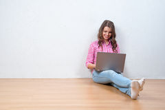 Young creative woman sitting in the floor with laptop Stock Image