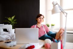 Young creative woman in a studio, resting. A startup of tailoring business. Young creative woman in a studio, resting with feet on desk. A startup of small royalty free stock photography