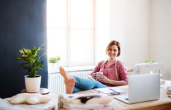 Young creative woman in a studio, resting. A startup of tailoring business. Young creative woman with coffee in a studio, resting with feet on desk. A startup royalty free stock image