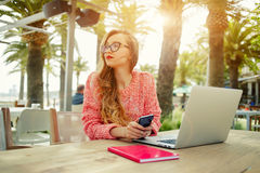 Young creative woman work on laptop while having breakfast on terrace Stock Images