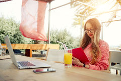 Young creative woman work on laptop while having breakfast on terrace. Attractive female freelancer reading notebook while sitting at wooden table front open Stock Image
