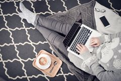 Young creative woman working with laptop. Young creative woman sitting in the floor and working with laptop, cup of coffee and mobile phone, top view Stock Images