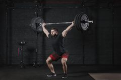 Young crossfit athlete lifting barbell overhead at gym. Man practicing functional training powerlifting workout exercises. Young crossfit athlete lifting barbell stock image