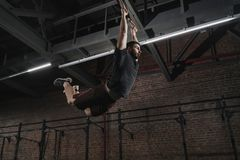 Young crossfit athlete swinging on gymnastic rings doing pull-ups at gym. Workout exercises stock image