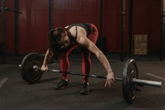 Young crossfit woman preparing barbell for lifting weight at the gym stock photos