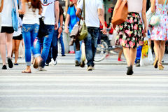 Young crowd on zebra crossing. Motion blurred pedestrians crossing sunlit street Stock Photos