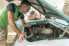 Young Cuban men discussing car renovation project Royalty Free Stock Image
