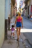 Young Cuban mother going for a walk with her girl toddler in Hav. Cuba, Havana - 07 April, 2016: a young Cuban mother going for a walk with her girl toddler in Stock Photos