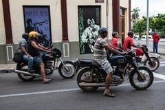 Motorbikes driving in the street of Santiago de Cuba. Waiting on traffic light stock photos
