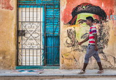 Young cuban walks by a Che Guevara portrait in Old Havana Stock Photography