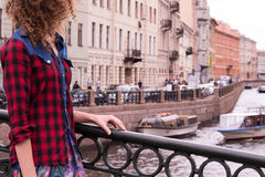 Young curly cute teenage girl standing on the bridge of the Moika River in St. Petersburg, Russia royalty free stock image