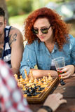 Young curly female play chess at camp Royalty Free Stock Photo