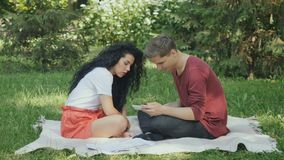 Cute couple uses smartphone in park on plaid stock footage