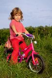 Young curly girl biker rests in the field Stock Image
