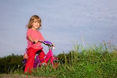 Young curly girl biker rests in the field Stock Photography