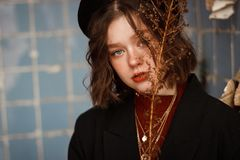 Young curly girl with blue eyes in black hat stock image