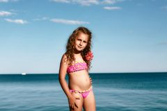 Young curly girl in a pink swimsuit relaxing on the beach, Black Sea, Odessa, Ukraine, place for text set stock photos