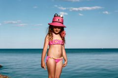 Young curly girl in a pink swimsuit relaxing on the beach in the hat, Black Sea, Odessa, Ukraine, place for text set royalty free stock images