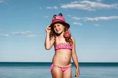 Young curly girl in a pink swimsuit relaxing on the beach in the hat, Black Sea, Odessa, Ukraine, place for text set stock image