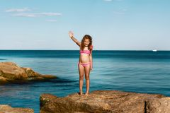 Young curly girl in a pink swimsuit relaxing on the rocks on the beach, the Black Sea, Odessa, Ukraine, a place for text, a set stock photography