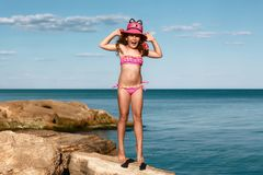 Young curly girl in a pink swimsuit relaxing on the rocks on the beach, jumps in a hat Black Sea, Odessa, Ukraine, place for text royalty free stock image