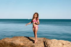 Young curly girl in a pink swimsuit relaxing on the rocks on the beach, standing on her fingers Black Sea, Odessa, Ukraine, place royalty free stock image