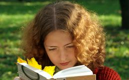 Young Curly Girl Reads A Book In A City Park. The Book Contains A Bright Yellow Autumn Leaf Stock Images