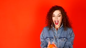 Young curly girl throws orange on a coral background in the studio.  stock video footage