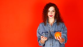 Young curly girl throws orange on a coral background in the studio.  stock video