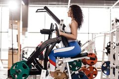 Young curly good fit girl dressed in sports clothes is doing exercise on the sports equipment in the modern gym full of stock image