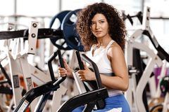 Young curly good fit girl dressed in sports clothes is doing exercise on the sports equipment in the modern gym full of royalty free stock photos