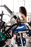 Young curly good fit girl dressed in sports clothes is doing exercise on the sports equipment in the modern gym full of royalty free stock photo