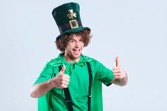 A young curly-haired man in St. Patrick`s suit shows his finger. A young curly-haired man in St. Patrick`s suit shows his finger up on a gray background Royalty Free Stock Photography