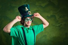 A young curly-haired man in St. Patrick`s suit shows his finger. Up on a green background Stock Photos