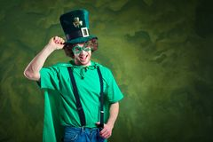 A young curly-haired man in St. Patrick`s suit shows his finger. Up on a green background Stock Photo