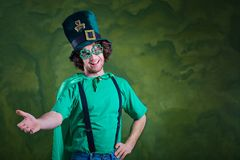 A young curly-haired man in St. Patrick`s suit shows his finger Royalty Free Stock Photo