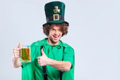 A young curly-haired man in the suit of St. Patrick with a mug o. F beer in his hand on a gray background Royalty Free Stock Image