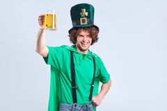 A young curly-haired man in the suit of St. Patrick with a mug o. F beer in his hand on a gray background Stock Images