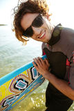 Young curly man in eyeglasses and swimsuit holding surf board. Close up portraut of a young curly man in eyeglasses and swimsuit holding surf board at the beach Stock Image