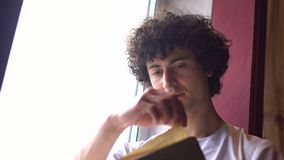 Young Curly Man in White Cloth is Sitting on Window Sill and Reading Book with Daylight from Window. 4k UHD stock footage