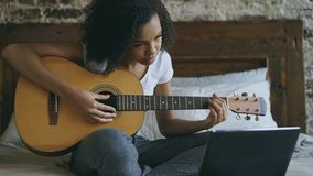 Young curly mixed race girl concentraing learning to play guitar using laptop computer sitting on bed at home