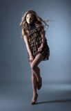 Young curly model posing in leopard print dress Royalty Free Stock Images