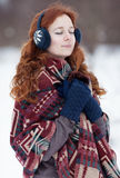 Young curly red-haired woman in blue gloves and headphones Royalty Free Stock Images