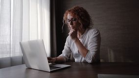 Young curly woman in glasses pensively typing on a laptop in the office stock footage