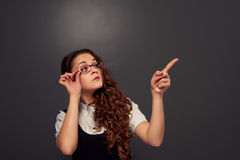 Young curly woman in glasses pointing at empty copyspace Royalty Free Stock Photography