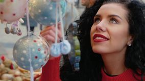 Woman looks at the Christmas decorations. A young curly woman looks at the Christmas baubles, toys and decorations in a shop window during the Christmas season stock video footage