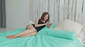 Young curly woman lying in the bed with tablet pc stock footage