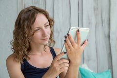 Young curly woman lying in the bed with tablet pc. stock image
