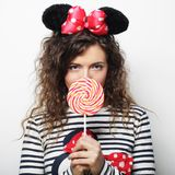Young curly woman with mouse ears holding lollipop. Young happy curly woman with mouse ears holding lollipop Stock Images